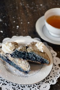 2 Blueberry Scones With Whipped Cream On A Doily With A Cup Of Oolong Tea.