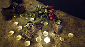 Candlelit Shoes On The Danube Memorial With Roses At Night In Budapest, Hungary.