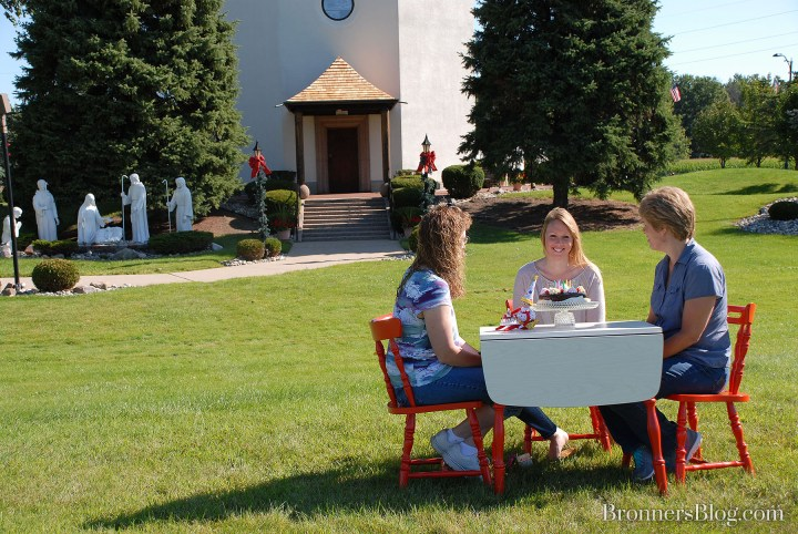 Friends enjoy a cake outside of Bronner's Silent Night chapel