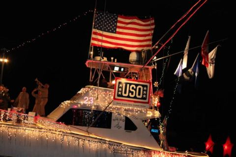 boat decorated red, white and blue with a USO theme and performers for Christmas boat parades in Florida