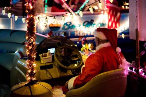 Santa in captain's chair of decorated boat for Christmas boat parades in Florida