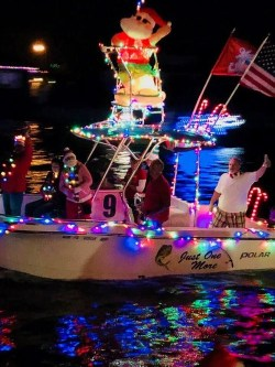 fishing boat decorated with colored lights, candy canes and an inflatable Santa