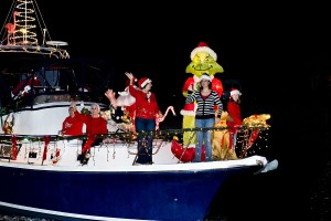 boat decorated with lights, inflatable Grinch and people in red shirts and Santa hats waving