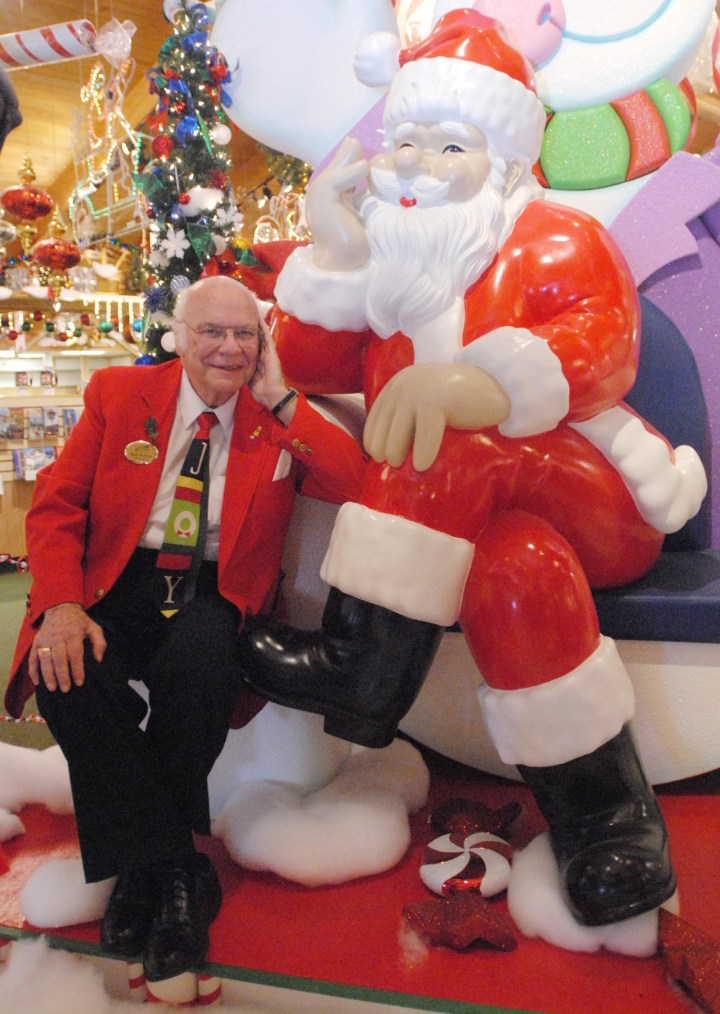 """Mr. Christmas"" poses with a life-size Santa in a photo taken by the Saginaw News."
