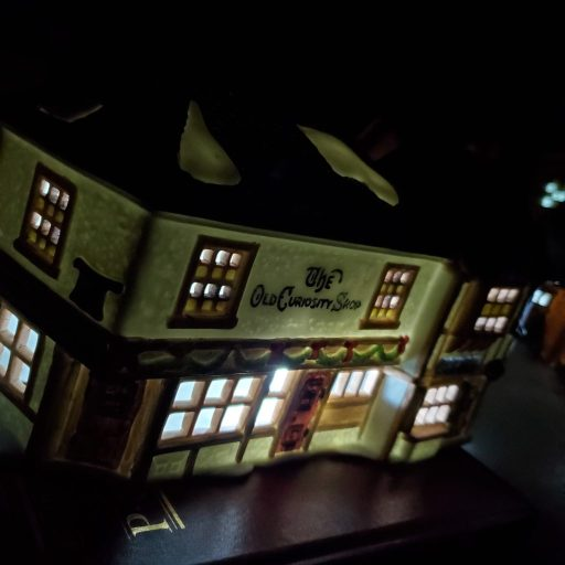 "lighted Dickens' Village ""Old Curiosity Shop"" set atop books on top of bookcase in the dark"