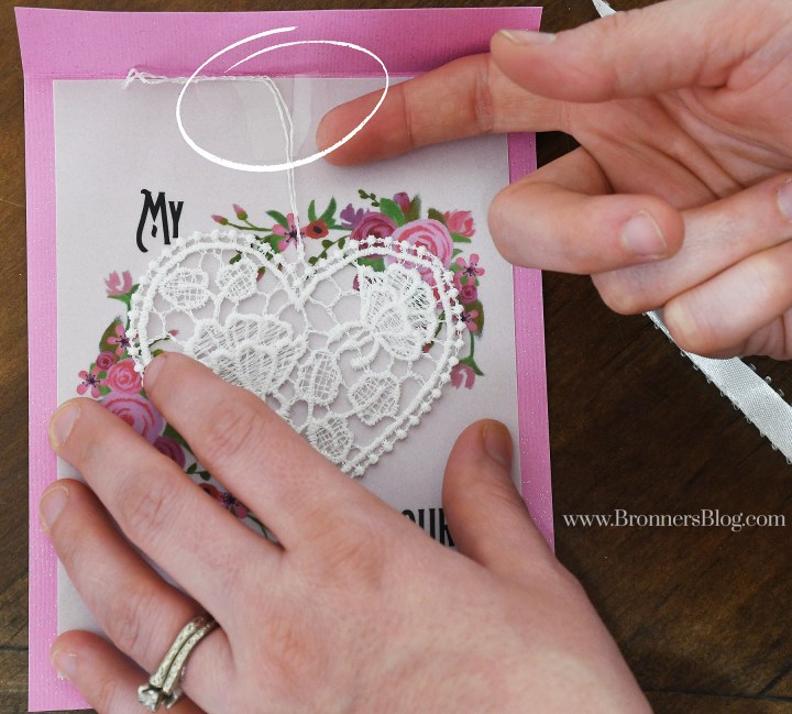 Step 3: Tape the lace heart ornament beneath the paper fold.