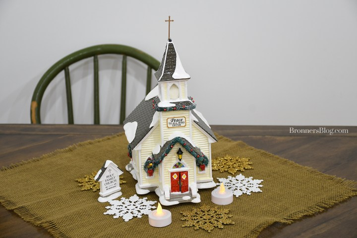 """Holy Family Church"" displayed on table atop burlap with gold and white snowflakes and battery-operated tea lights"