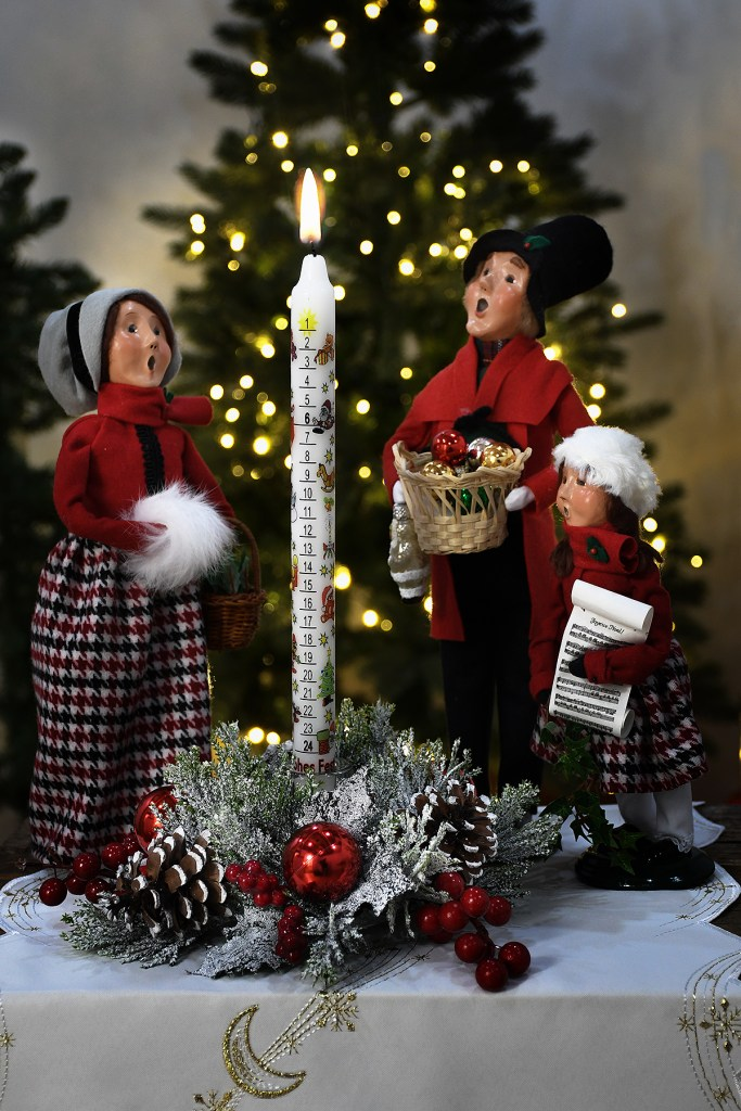 made in Germany Advent countdown taper candle in evergreen candle holder on table surrounded by Byers' Choice carolers with a lighted Christmas tree in the background