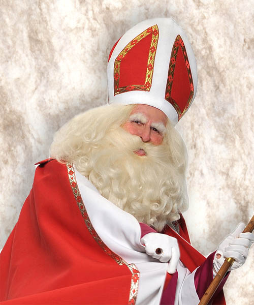 Father Joseph Marquis dressed in red, white and gold mitre and robe with full white beard and hair as St. Nicholas, part of how Germany celebrates Christmas