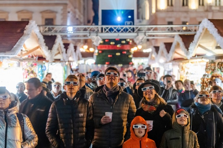 Crowd wearing 3D glasses to watch the light show at Basilica Christmas market in Budapest Hungary.