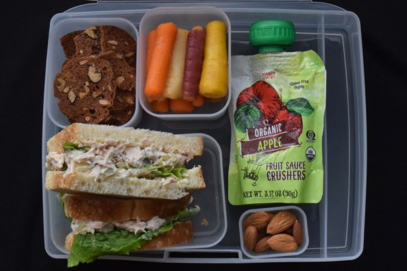 bento box with carrots sandwich nuts crackers and apple sauce pouch