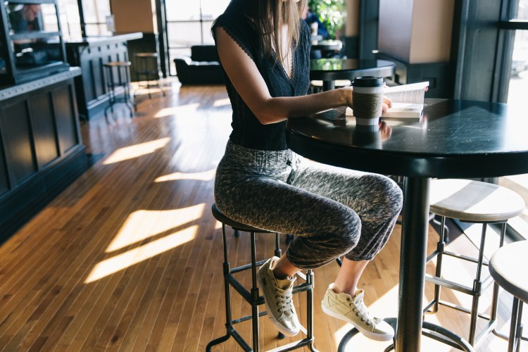 Woman sitting at high top table drinking coffee - wearing sneakers with black lace bodysuit, grey jogger pant & sneakers.
