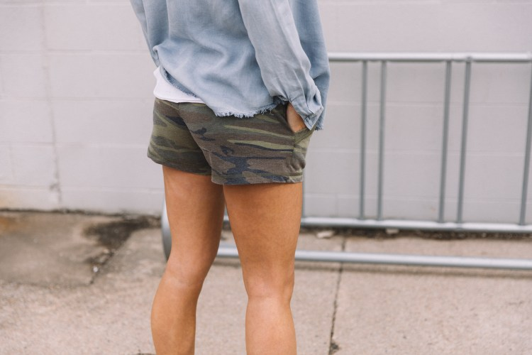 Close up photo of women wearing a BKE chambray button-down top, White Crow white lace-up tank top, and french terry camo shorts.