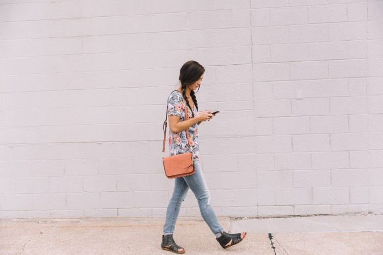 Women walking outside and texting on mobile phone while wearing clothing from the Buckle, including a White Crow floral t-shirt, Daytrip Refined skinny jeans, Violet Ray brand crossbody purse, and black leather Roan gladiator sandals.