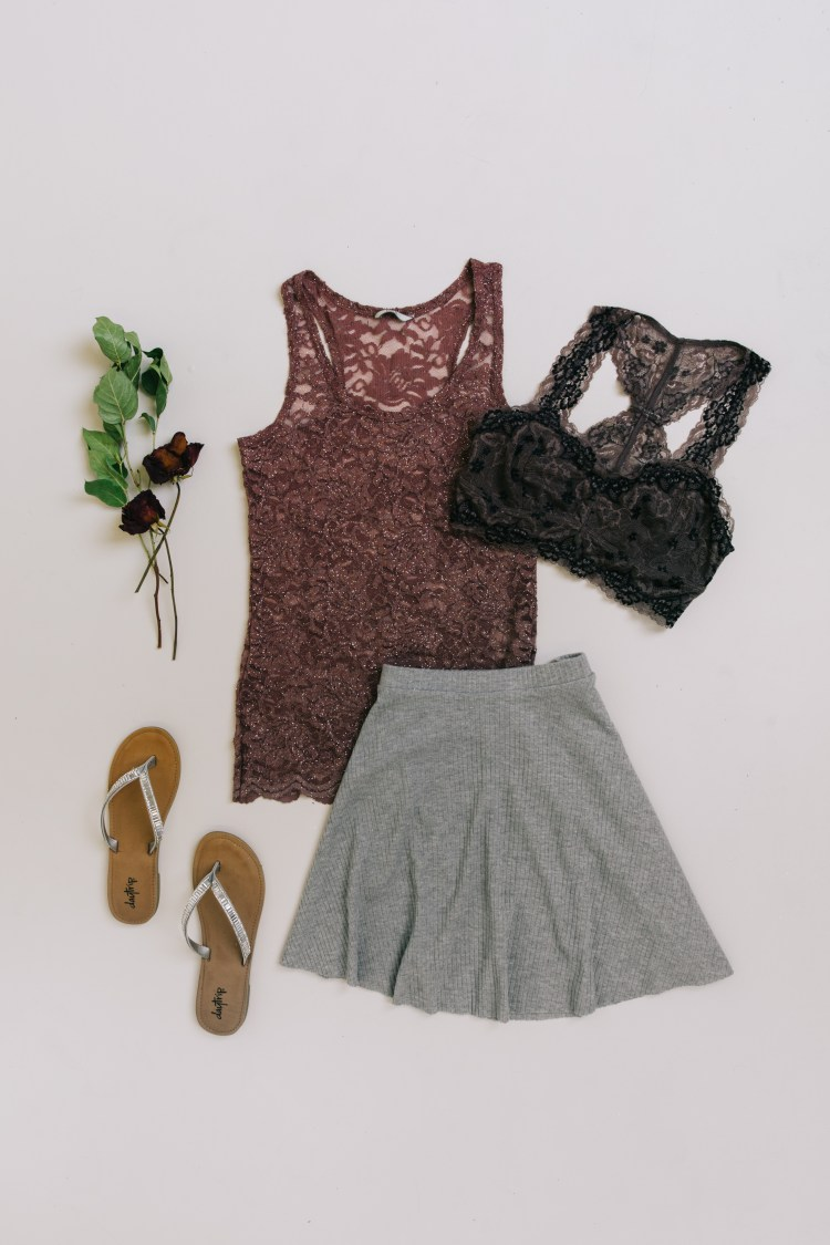 Laydown of a grey skater skirt, mauve lace tank top, and black bralette.