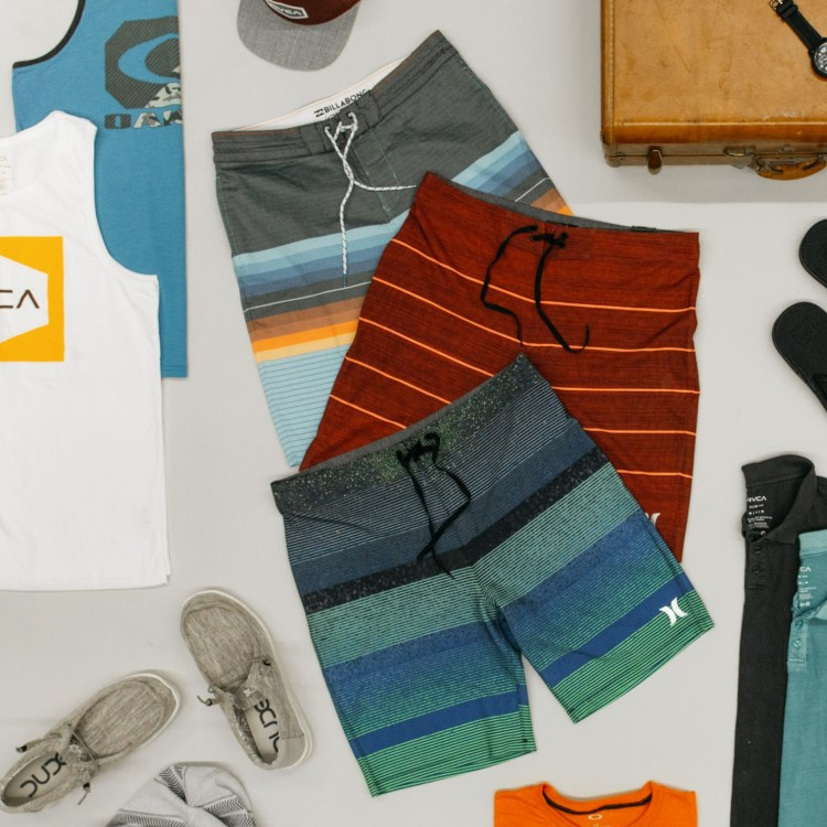 Clothing for a vacation laid out, including boardshorts, tank tops, and shoes.