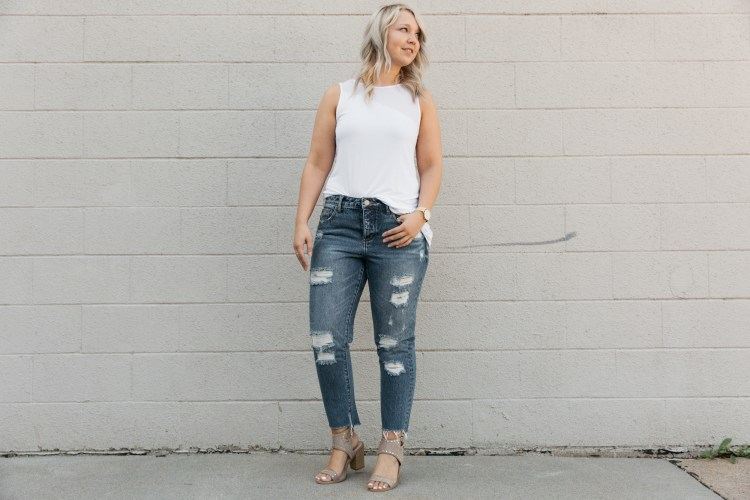Blonde girl in Gilded Intent jeans with a step hem and heels. She is in a white shirt.