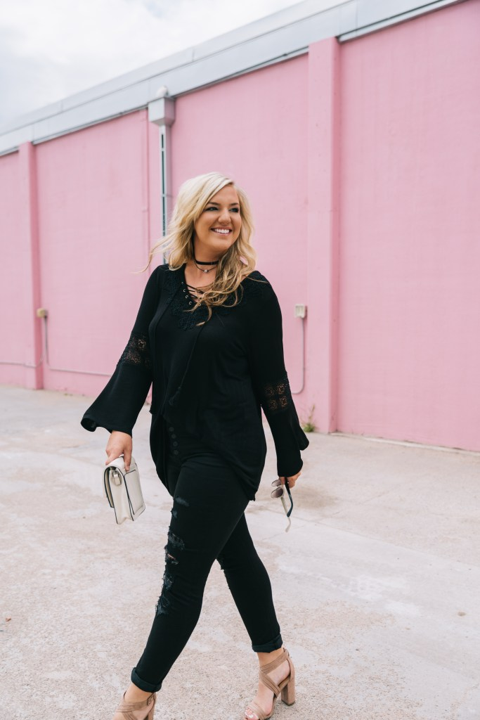 Tie-up shirt with bell sleeves and lace detailing paired with black denim on plus-size model.