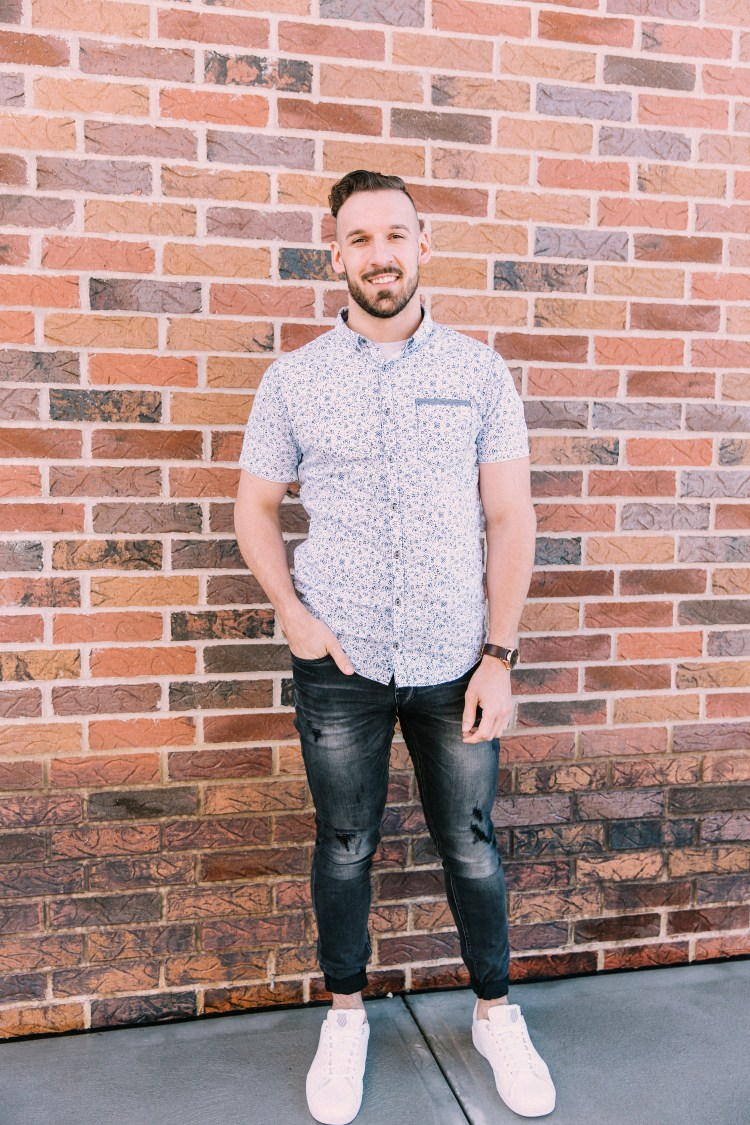 Man wearing a Departwest short-sleeve button-up shirt with a light blue micro-floral print, Departwest Trouper skinny jeans in a dark wash, white K-Swiss sneakers, and a Nixon brown leather wrist watch.