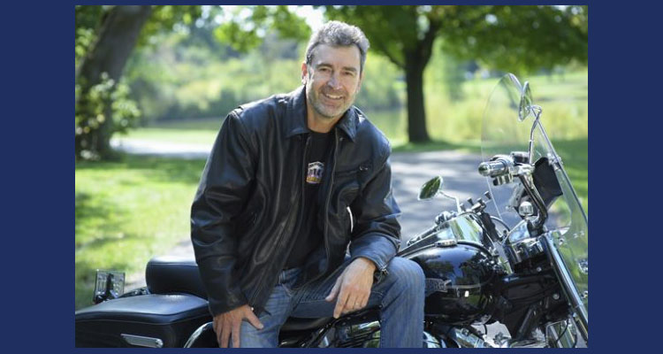 Man wearing a black shirt and jacket sitting on a motorcycle