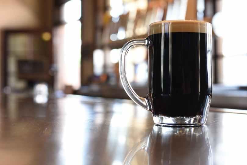 clear glass mug with black liquid