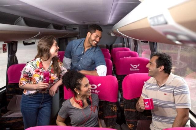 quatro pessoas alegres de gêneros diferentes mostrando na imagem o que é a Buser e como viajar