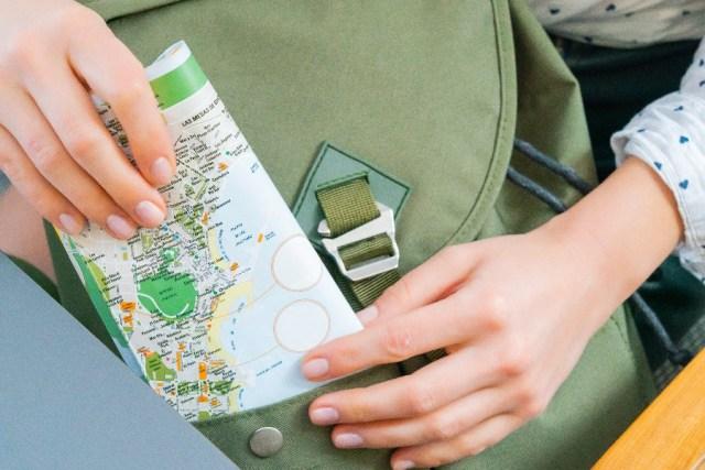 imagem de mãos femininas encostadas em uma mochila e segurando um mapa que remete que a escolhe do destino influencia na escolha da melhor época para viajar