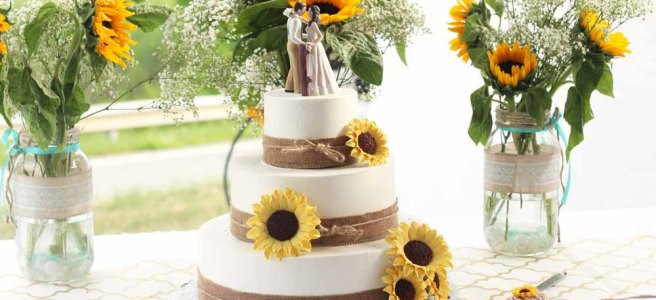 summer wedding by Pierrot Catering. Buttercream wedding cake with burlap ribbon and sugar sunflowers.