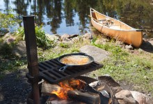 Fish in a frying pan with a canoe in the background
