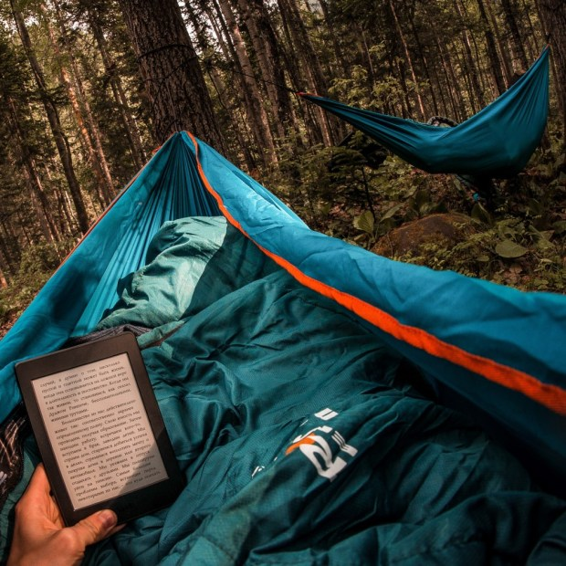 reading a kindle while hammock camping
