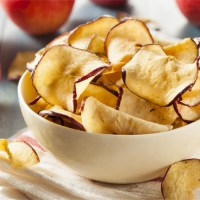 homemade baked apple chips in a bowl at a campsite