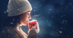 woman drinks a hot drink in the winter snow