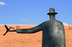 scultura di Folon, raffigura un uomo con cappello, braccio teso su cui è posato un uccellino