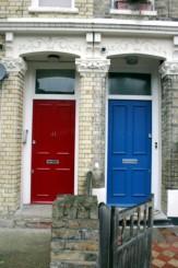 primo piano di due portoncini d'ingresso di due case londinesi: a sinistra il portoncino di colore rosso, a destra di colore blu
