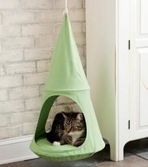 Un gatto dentro una cuccia di stoffa sospesa