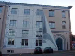 foto di facciata di palazzo, cui è stato aggiunto, in fotomontaggio, il progetto