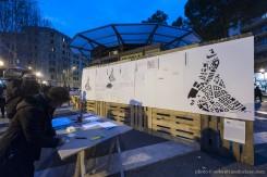 Il Progetto dei TAU Studio, Esperimenti urbani, piazza S. Maria Liberatrice (foto di Sebastiano Luciano)– alt: su di un pannello è riprodotta la mappa del quartiere e alcune indicazioni; un passante guarda il lavoro.