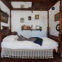 letto a baldacchino in legno circondato da piccoli oggetti