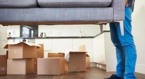 immagine trasloco casa: scatoloni e divano portato da 2 persone