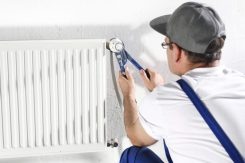 aiuto in casa - un idraulico lavora su un termosifone