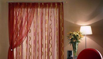 Come scegliere le tende giuste? Nella foto tendaggi trasparenti rossi con onde verticali dorate