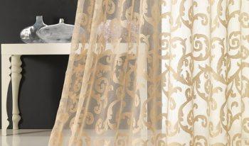 Come scegliere le tende giuste. Nella foto, tendaggio trasparente beige con arabeschi in tono