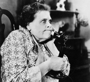chiamate indesiderate foto b/n signora anziana risponde a un vecchio telefono