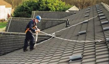 edilizia arobatica operatore sul tetto agganciato alla linea vita con corde di sicurezza