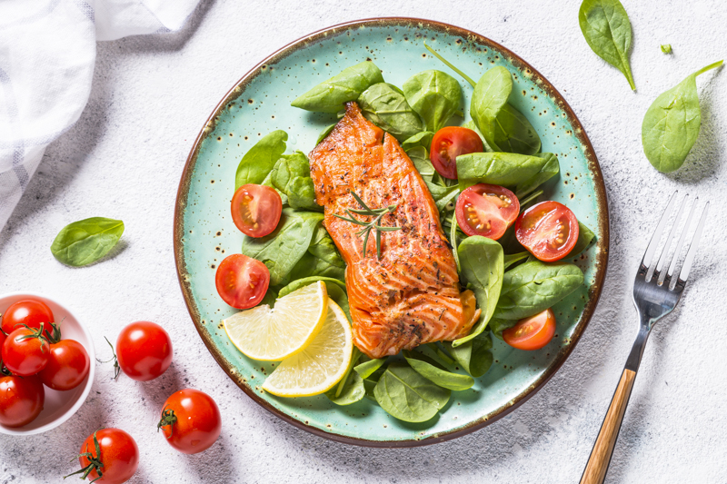 Baked salmon fish fillet with fresh salad from spinach and tomatoes. Top view on white background.