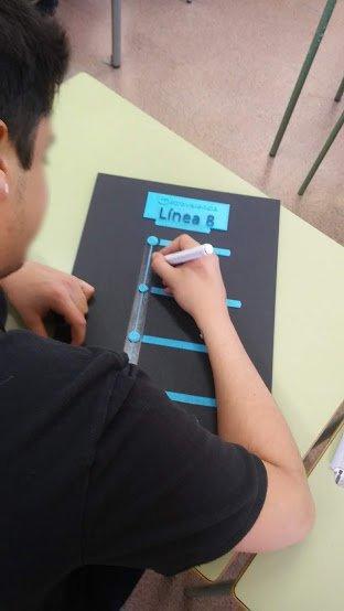 Fotografía de un alumno repasando una línea impresa en 3D con un rotulador