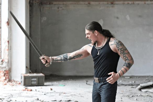 Tattooed man holding medieval sword