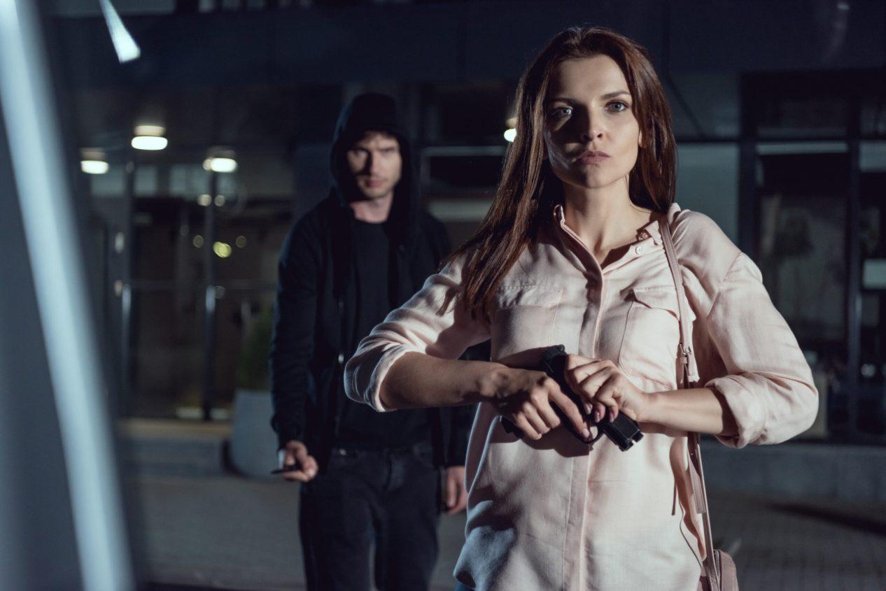 woman with gun looking at camera near thief at night