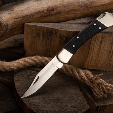 A sharp pocket knife on a tree stump and rope. Top.