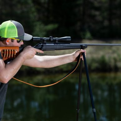 A man aiming a hunting rifle resting on shooting sticks.